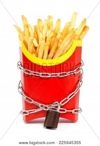 Ban on potatoes for diet and cholesterol reduction. The French fries in the packing box are wrapped around the chain and closed on a padlock. White isolated background stock photo