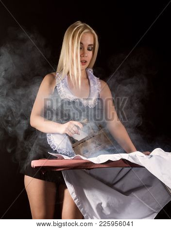 sexy blonde woman in housekeeper suit, ironing white shirt with old iron. retro style. housewife concept stock photo