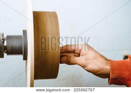 Wood turners using sandpaper polished wood on a lathe stock photo
