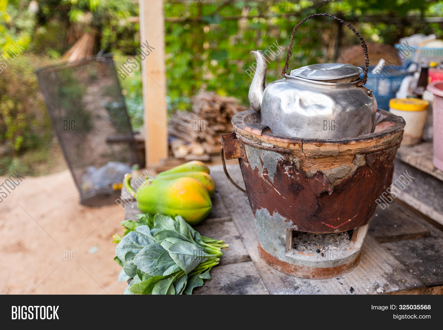 Old Thai Kettle On Thai Charcoal Stove With Green Leafy Vegetables And Papaya Put On A Wooden Table