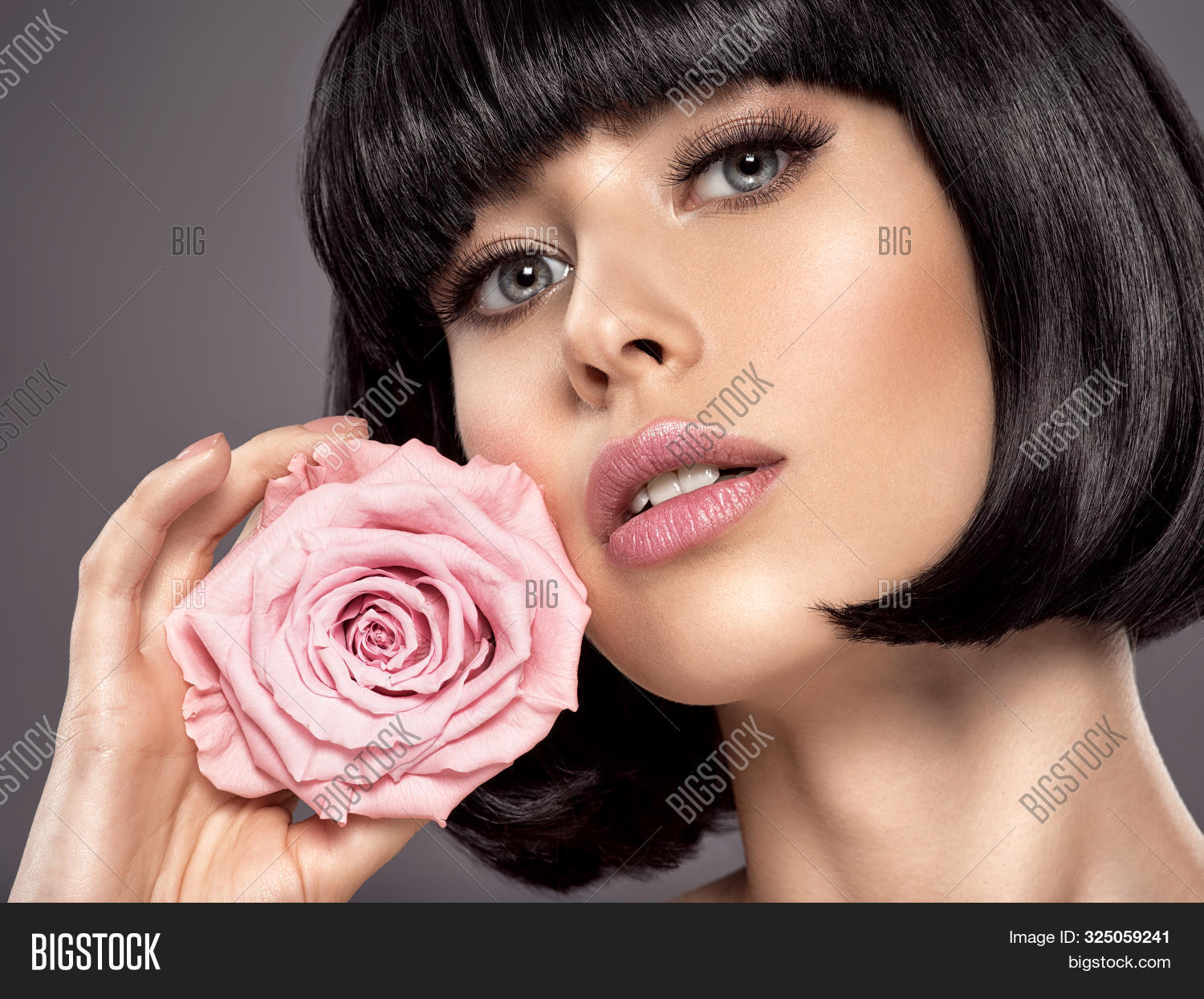 Woman with beauty short black hair holding rose flower. Fashion model with  straight hair. Fashion m