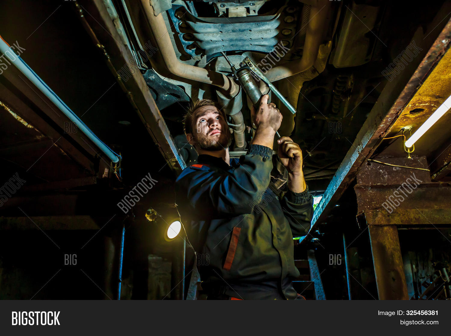 adult,auto,automobile,automotive,business,car,caucasian,engine,examining,expertise,fix,garage,indoors,industry,maintenance,male,man,manual,mechanic,mechanical,motor,occupation,oil,overalls,people,person,problem,repair,repairman,rust,service,shop,technician,tire,tool,under,vehicle,work,worker,working,young
