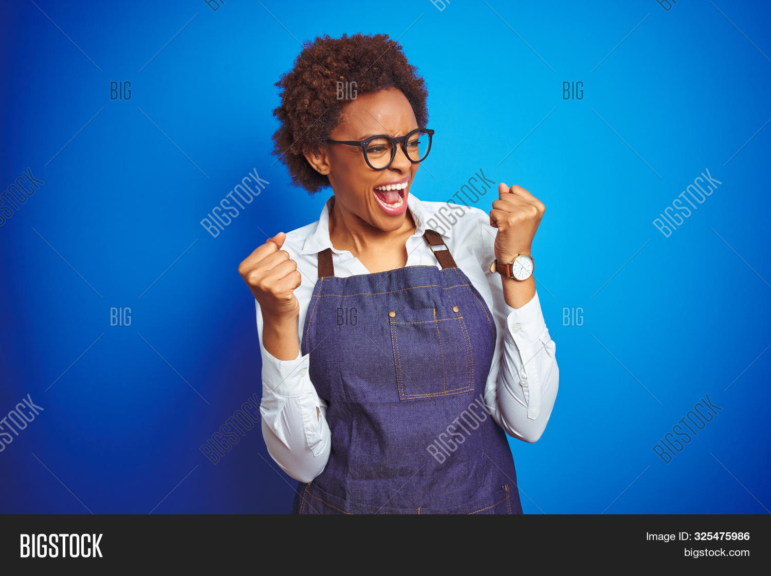 Young african american woman shop owner wearing business apron over blue background very happy and e