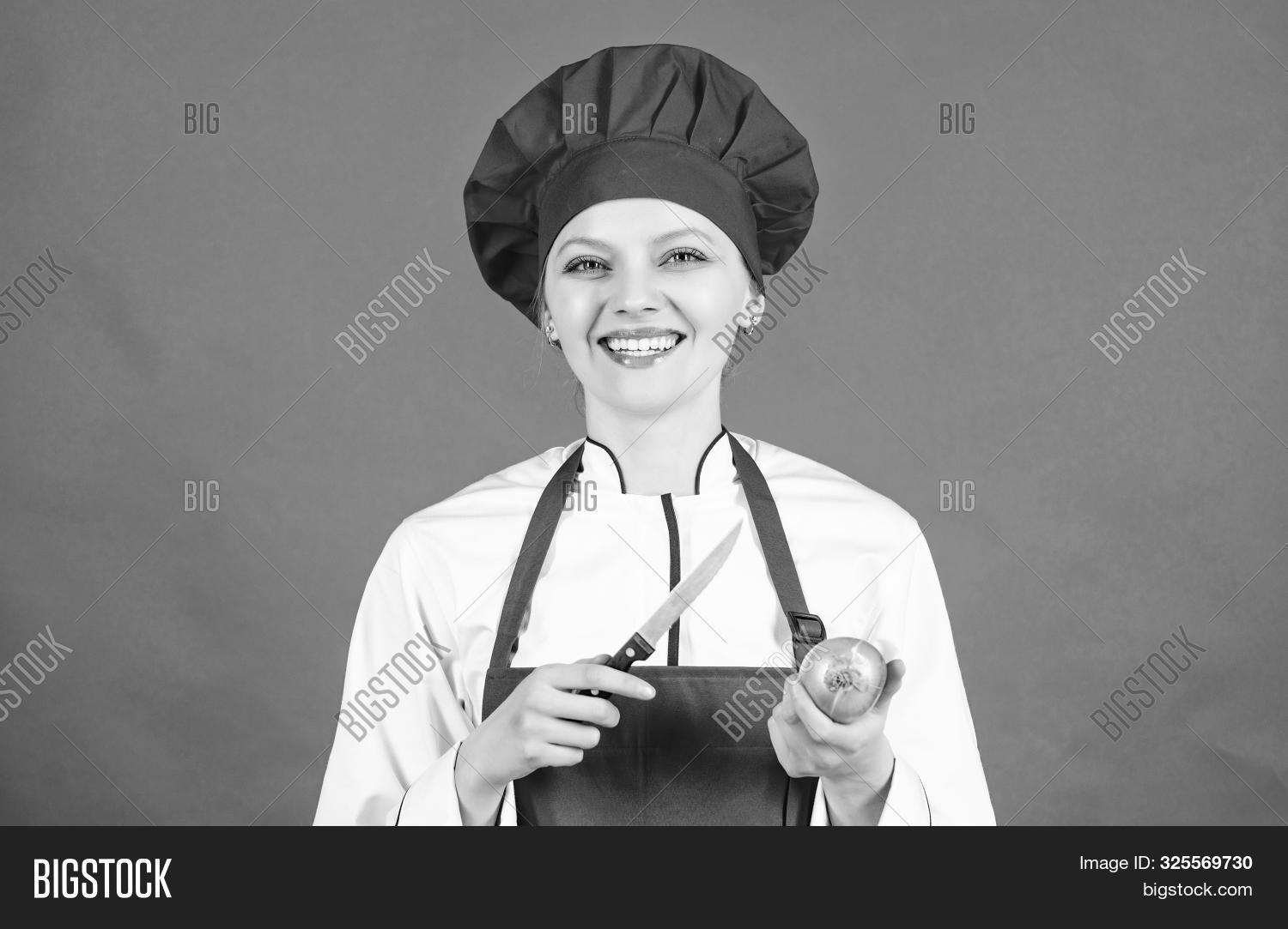 Cuisine. woman in cook hat and apron. happy woman cooking healthy food by recipe. Housewife with cooking knife and onion. professional chef in kitchen. Being hungry