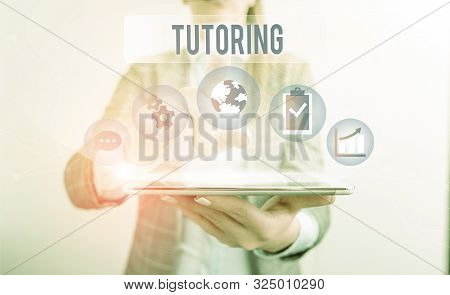 Conceptual hand writing showing Tutoring. Business photo showcasing An act of a demonstrating employed to administer knowledge to someone Female human wear formal work suit presenting smart device. stock photo