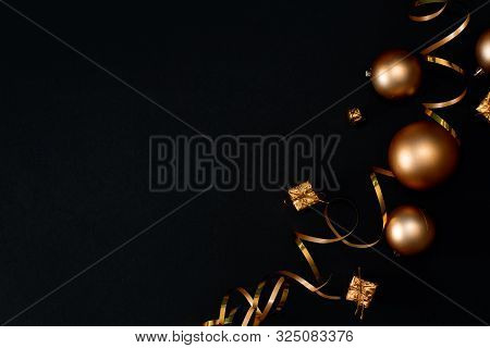 Holiday background ribbons on black. Holiday ribbons on black background. Gold confetti stock photo