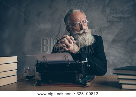 Close-up portrait of his he nice attractive bearded smart clever bewildered gray-haired professional creative publisher creating screen story novel over concrete wall background stock photo