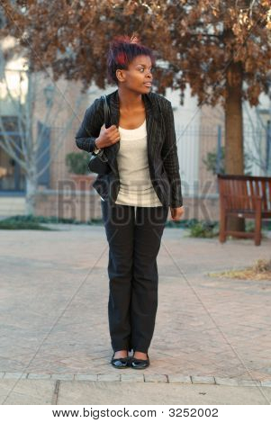 African American businesswoman commuter waiting for bus at stop stock photo