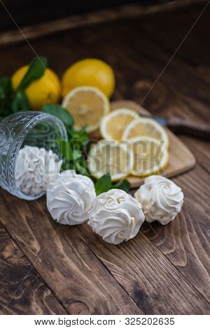 Yellow and white russian marshmallows zephyr on wooden table with lemon slices and mint leaves to show the flavour, close up stock photo