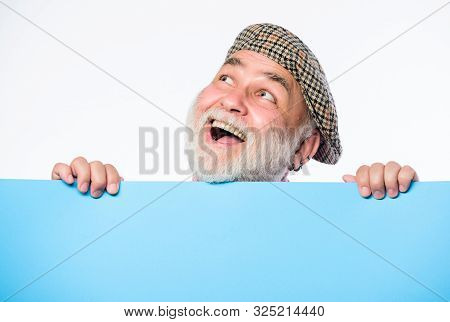 Senior bearded man peek out of banner place information. Advertisement elderly people. Charming pensioner in vintage hat hold poster information copy space. Public information. Announcement concept stock photo