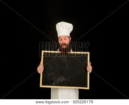 Restaurant chef show empty chalkboard. Advertising chef menu. Blank chalkboard with copy space for text. Male chef, cook or baker with blank board. Bearded chef holds blackboard. Business lunch menu stock photo