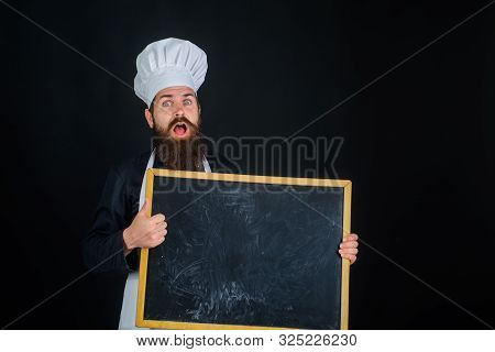 Chef. Man cook showing empty menu chalkboard with copy space. Smiling chef holds blackboard. Cooking, advertisement and food concept - happy male chef, cook or baker with blank board shows thumb up stock photo