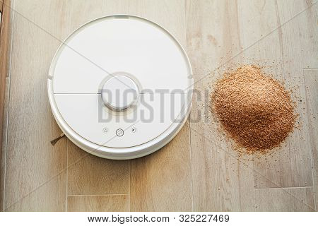 Smart home. Robot vacuum cleaner performs automatic cleaning of the apartment at a certain time stock photo