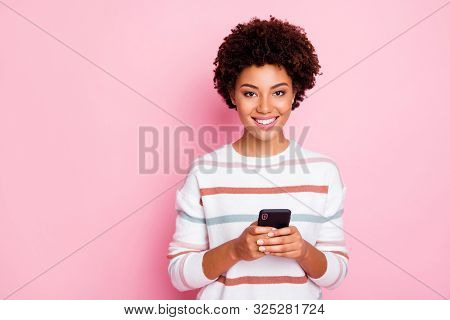Photo of pretty dark skin curly lady holding telephone addicted to internet reposts and comments wear white striped pullover isolated pastel pink color background stock photo