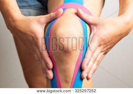 Kinesiotaping, kinesiology. Female athlete with kinesiotape, muscle tape on knee stock photo