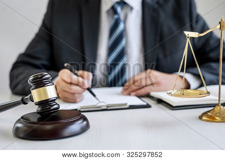 Male lawyer or judge working with contract papers, Law book and wooden gavel on table in courtroom, Justice lawyers at law firm, Law and Legal services concept. stock photo