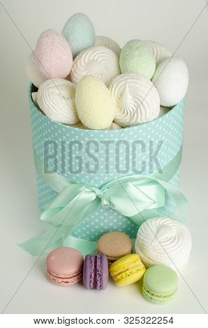 Colorful french macaroons or macarons, meringues and easter eggs in the gift box on white background. Greeting card. Easter holiday concept stock photo