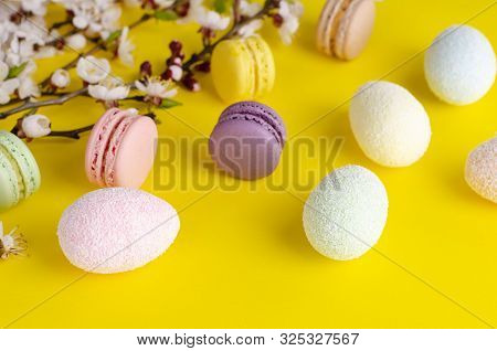 Multicolored decorative Easter eggs and sweet macarons or macaroons decorated with blooming apricot flowers on yellow background. Copy space. Greeting card and Happy Easter concept. Top view stock photo