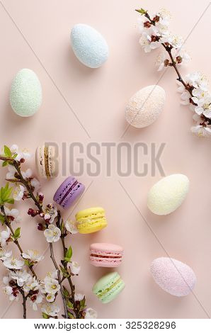 Multicolored decorative Easter eggs and sweet macarons or macaroons decorated with blooming apricot flowers on pastel pink background. Copy space. Greeting card concept. Top view. Vertical stock photo