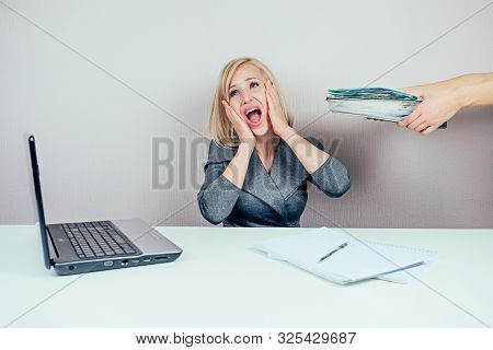 attractive smart blonde multitasking woman business lady in stylish business suit working with laptop and a bunch of folders screams in panic in office . business concept and deadline stock photo