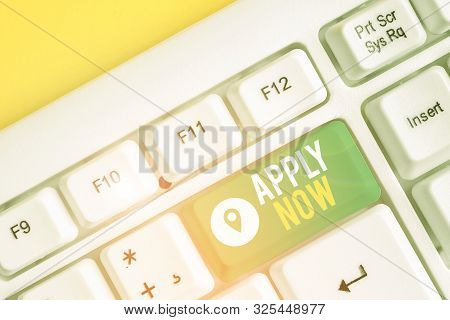 Text sign showing Apply Now. Conceptual photo An act of a demonstrating to acquire the job related to the profession White pc keyboard with empty note paper above white background key copy space. stock photo