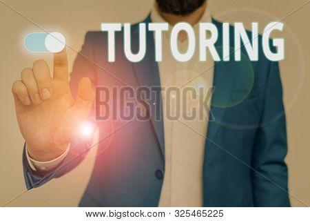 Conceptual hand writing showing Tutoring. Business photo showcasing An act of a demonstrating employed to administer knowledge to someone Male wear formal suit presenting presentation smart device. stock photo