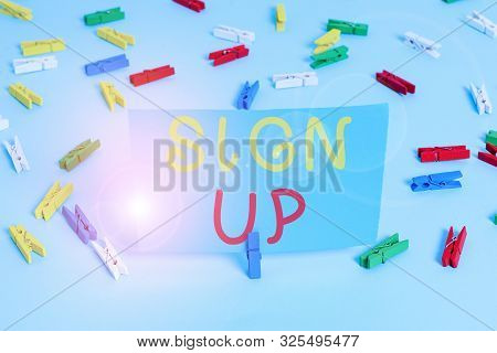 Handwriting text Sign Up. Concept meaning use your information to register in website team college or blog Colored clothespin papers empty reminder blue floor background office pin. stock photo
