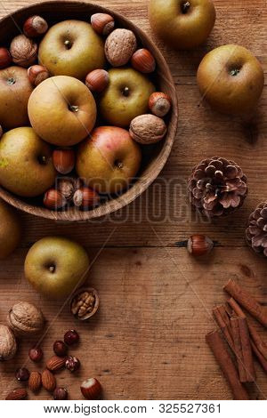 Autumn apples with nuts and cinnamon sticks on table, top view. Heirloom reinette apples.  stock photo