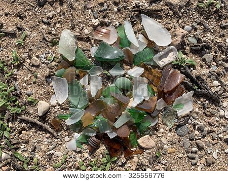 small pile of waterworn glass splinters washed up on beach sand stock photo