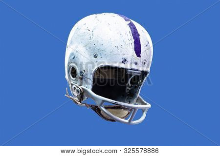 A worn and aged vintage old style American football helmet. Authentic and game-worn 1950s style football face mask and helmet stock photo