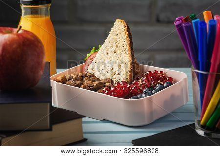 Diet Eco Healthy Dessert Nutrition in Plastic Box Copy Space. Freshness Citrus Juice in Glass Bottle, Multicolored Felt-tip Pens in Mug, Apple on Books on Blue Wooden Table. Brick Wall on Background stock photo