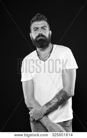 Brutal and masculine. Brutal caucasian man with long beard on black background. Brutal hipster with tattooed arms in casual style. Bearded man with brutal look. stock photo