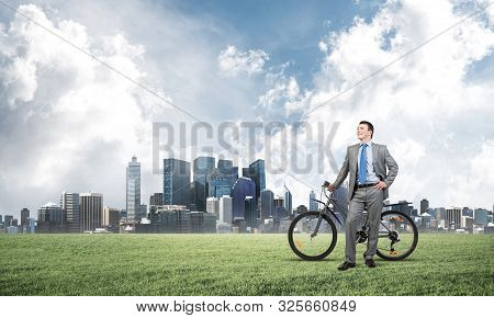 Good looking caucasian man in business suit posing on green meadow with bike. Happy businessman with bicycle relax on green grass at sunny day. Ecology transportation and environmental protection stock photo