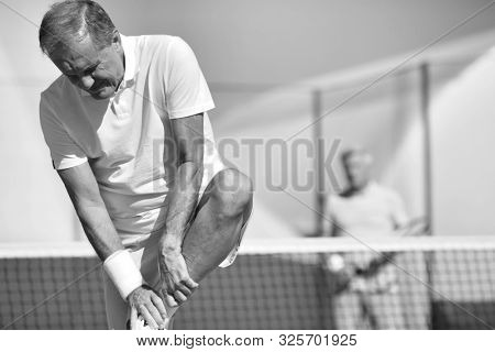 Mature man standing while suffering from leg pain during match at tennis court stock photo