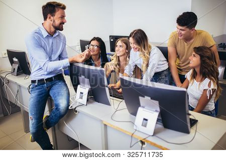 College students sitting in a classroom, using computers during class. stock photo