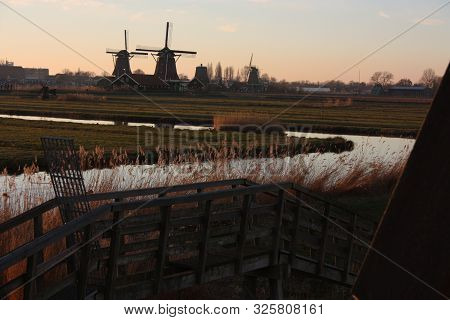 romantic sunset in red and yellow colors. the plain of the rural countryside of zaanse schans with its typical Dutch mills in Netherlands stock photo