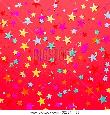 Festive red background with multicolor star confetti and streamers. Background for birthdays, christmas, anniversary. Holiday red background stock photo