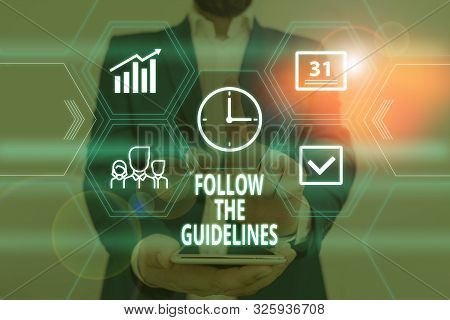 Text sign showing Follow The Guidelines. Conceptual photo Manual of Style Follow a Specified Rule Accordingly Male human wear formal work suit presenting presentation using smart device. stock photo