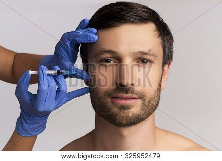 Male Injective Cosmetology. Middle Aged Man Receiving Wrinkle-Removing Injection Over White Studio Background. stock photo