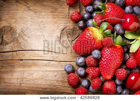 Berries on Wooden Background. Summer or Spring Organic Berry over Wood. Strawberries, Raspberries, B