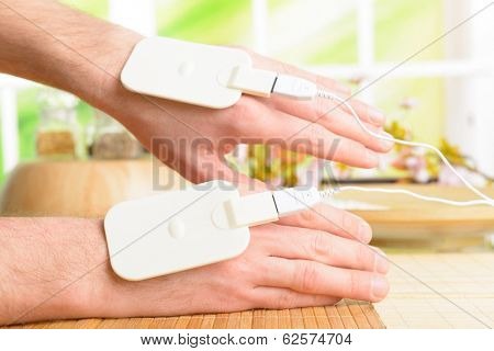 Electrotherapy, electrical stimulation using surface electrode pads with a conductor gel placed on the skin.  stock photo