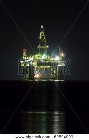 A close up night view of the oil drilling platform lit up on the coast of Limassol in Cyprus. The oil rig is floating in the Mediterranean sea and is ready for drilling for natural gas appraisal. stock photo