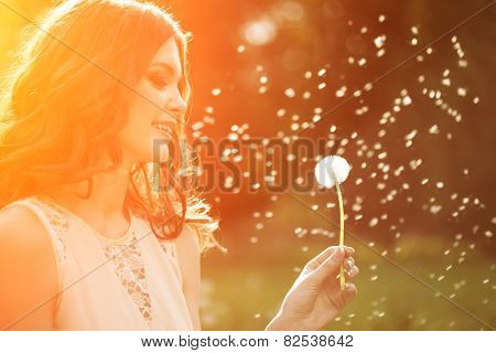 Young spring fashion woman blowing dandelion in spring garden. Springtime. Trendy girl at sunset in