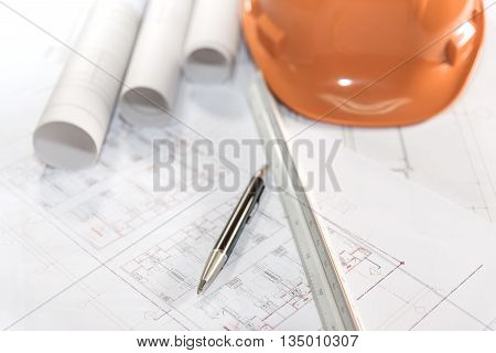 architectural plans project drawing and pen with blueprints rolls ruler and orange helmet architect engineering and contractor concept stock photo