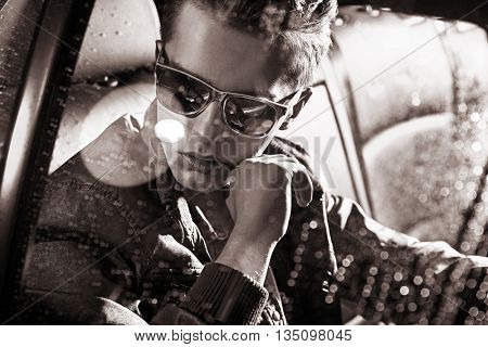 Handsome fashionable yonug man sitting in a car stock photo