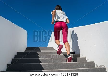 Stairs climbing running woman doing run up steps on staircase. Female runner athlete going up stairs