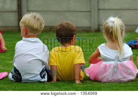three caucasian children: two boy toddlers and a girl child sitting on the lawn in the garden watching other kids playing stock photo