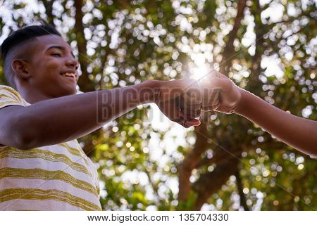 Youth culture young people group of male friends multiethnic teens outdoors teenagers together in park. Happy boys meeting kids shaking hands smiling. Concept of racism and integration of races stock photo