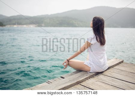 Yoga and meditation concept.Woman meditating in sitting yoga position on pier.Woman alone practicing mindfulness meditation to clear her mind.Zen,meditation,peace concept