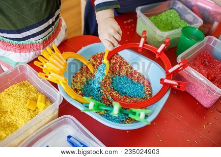 Toddlers playing with sensory bin with colourful rice on red table. stock photo